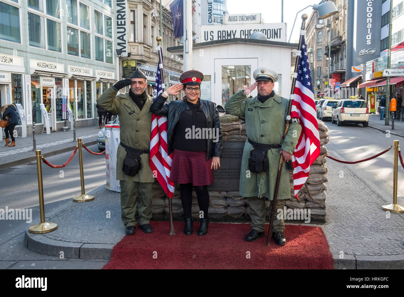 Los turistas posando con los soldados americanos en el Checkpoint Charlie, en Berlín, Alemania Imagen De Stock
