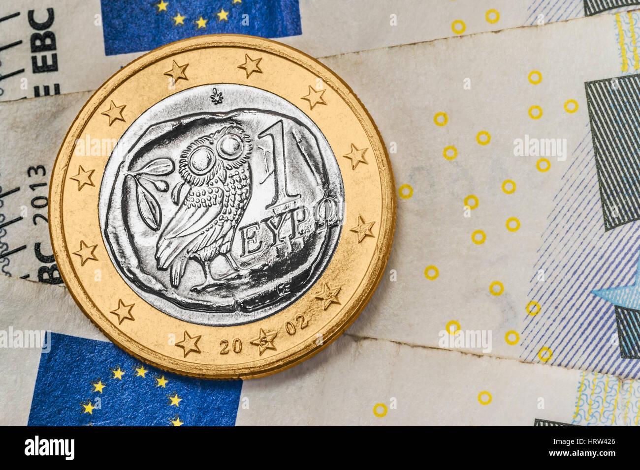 Una moneda de 1 euro de Grecia sobre los billetes en euros Foto de stock