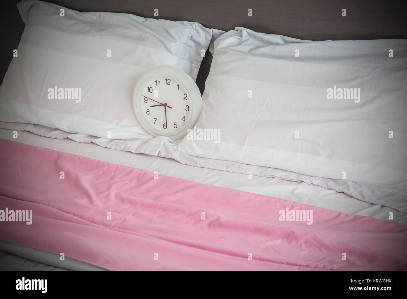 Alarma en la cama como despertar en la mañana concepto. Foto de stock