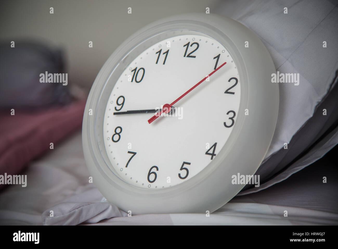 Cerca del reloj en la cama como despertar en la mañana concepto. Foto de stock
