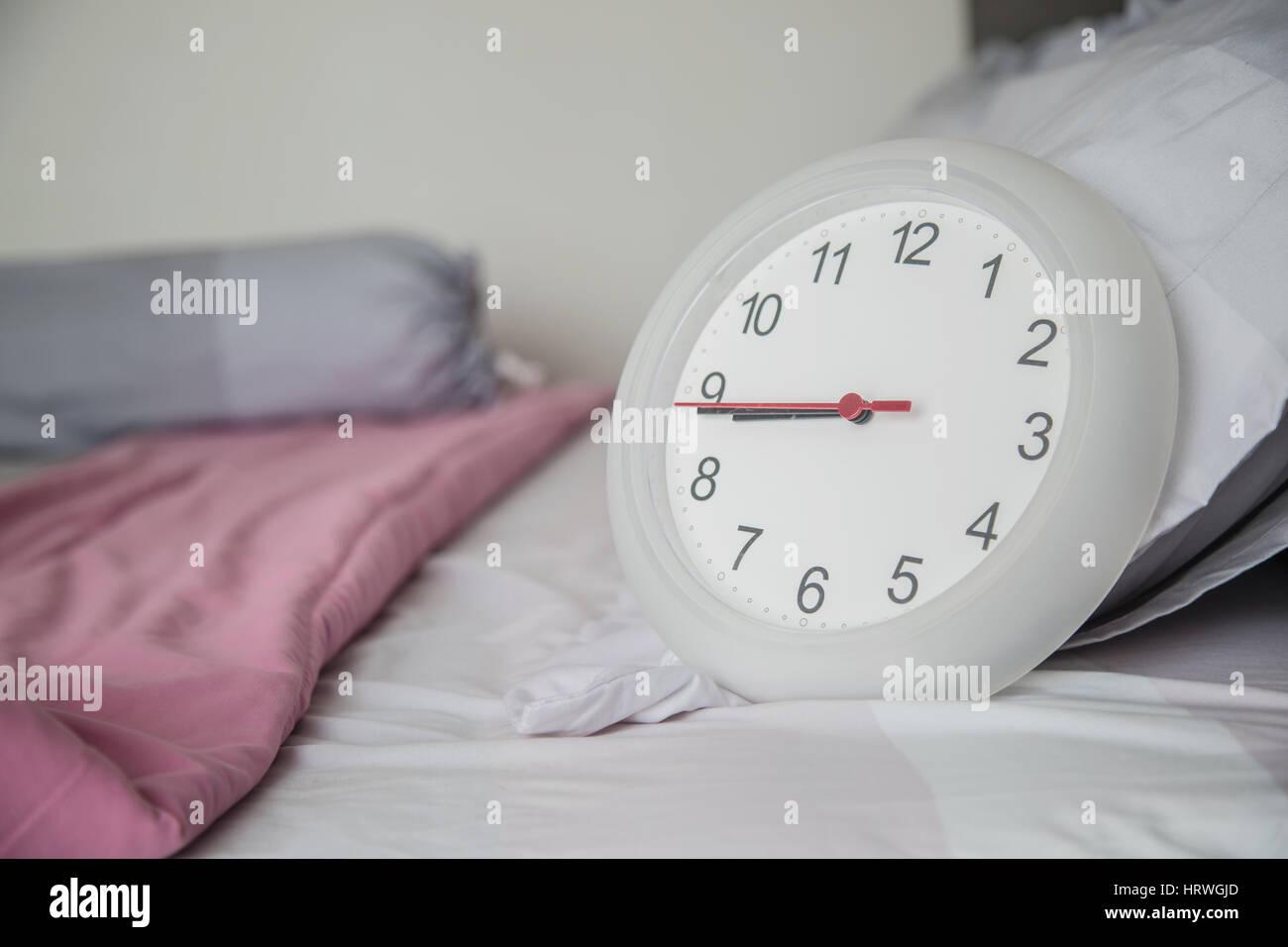 Reloj blanco en la cama como despertar en la mañana concepto. Foto de stock
