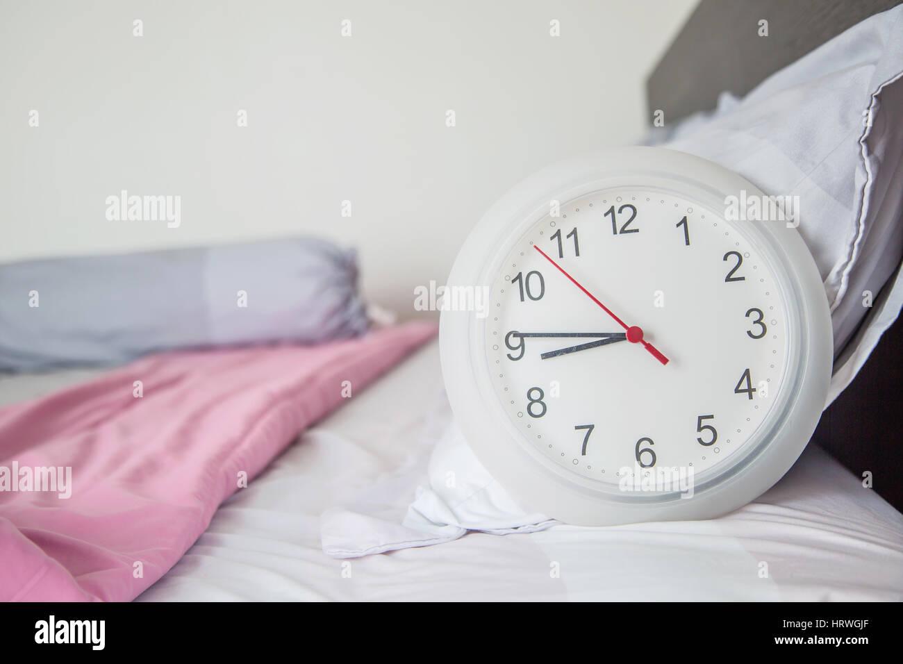 Cerca del reloj en la cama como la puesta en marcha mañana concepto. Foto de stock