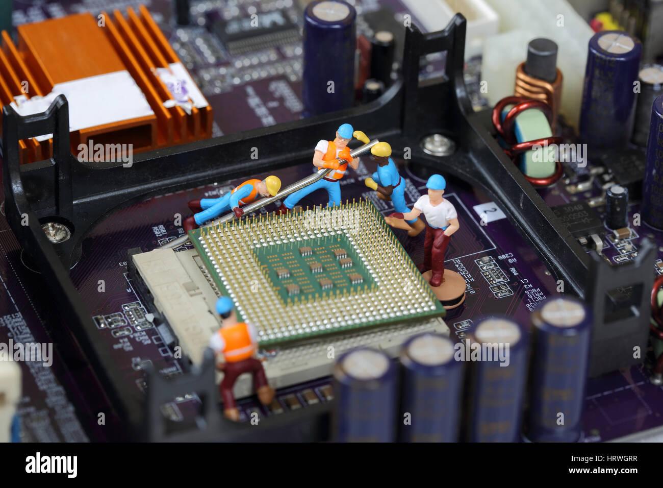 El enfoque selectivo de ingeniero en miniatura y trabajador fijo y reparar el procesador de la CPU, la placa base Foto de stock