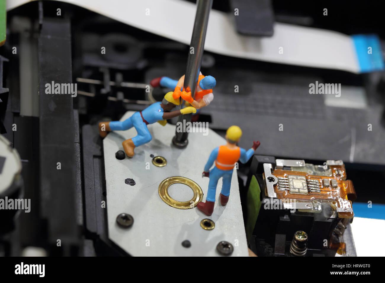 El enfoque selectivo de ingeniero en miniatura y trabajador fijo a quitar el tornillo con un destornillador para Foto de stock