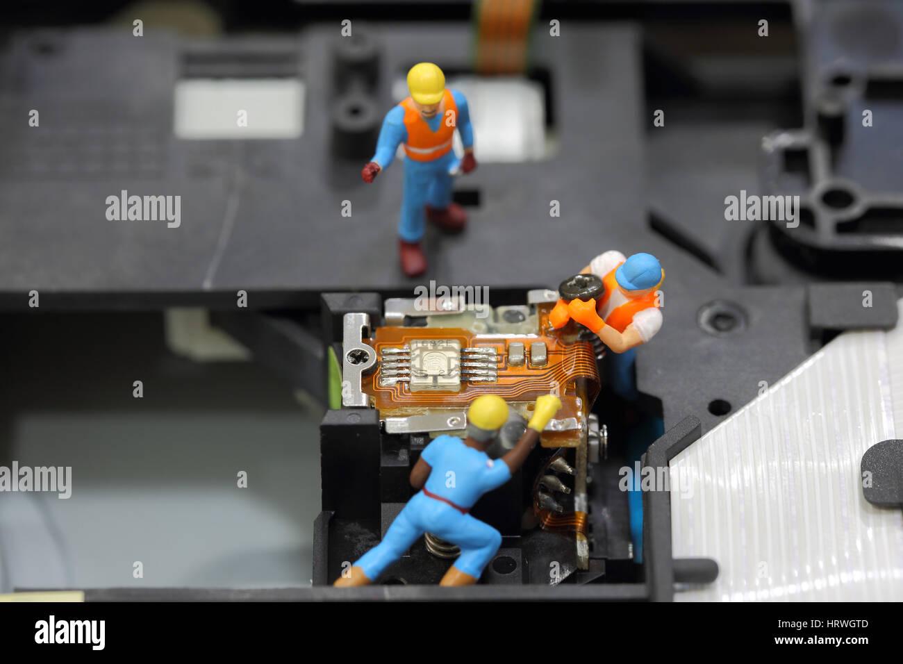 El enfoque selectivo de ingeniero en miniatura y trabajador para quitar el tornillo fijo para reparar el CD-ROM Foto de stock