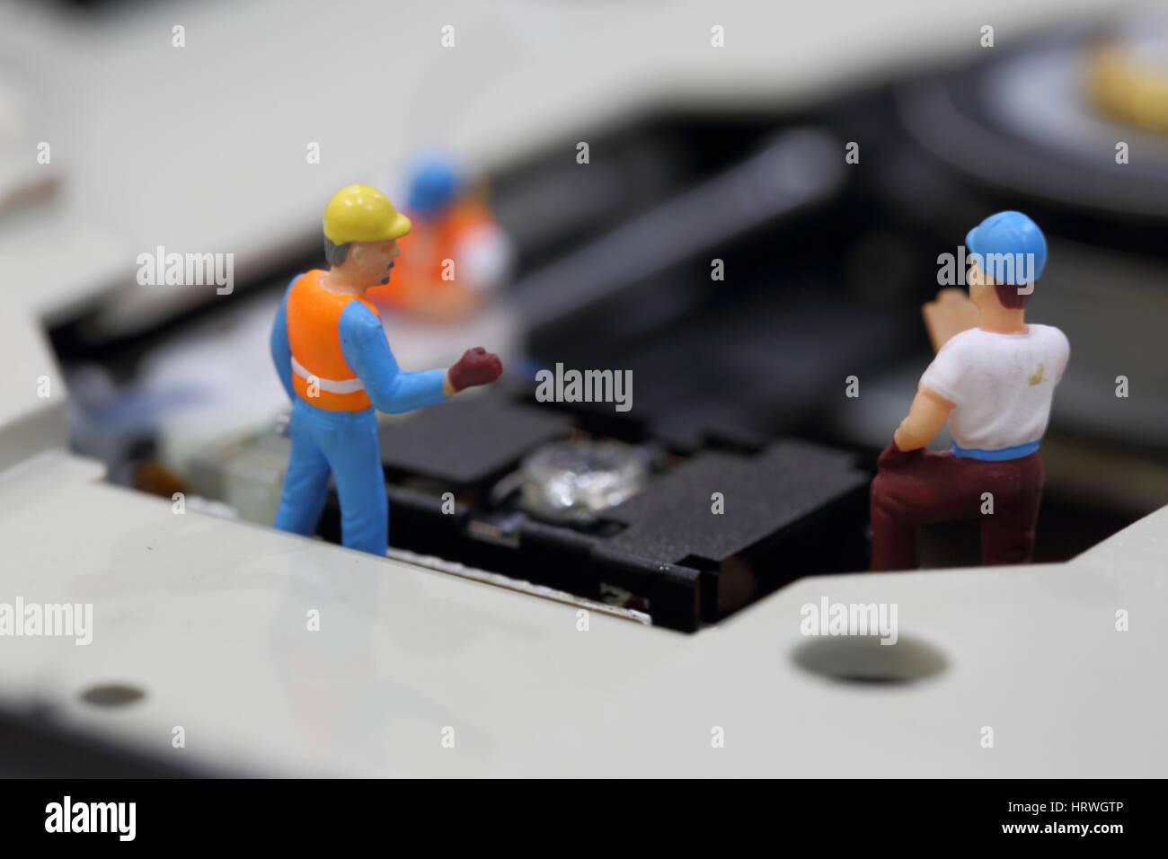 El enfoque selectivo de ingeniero en miniatura y reunión de los trabajadores y hablar de limpieza lector de CD ROM Foto de stock