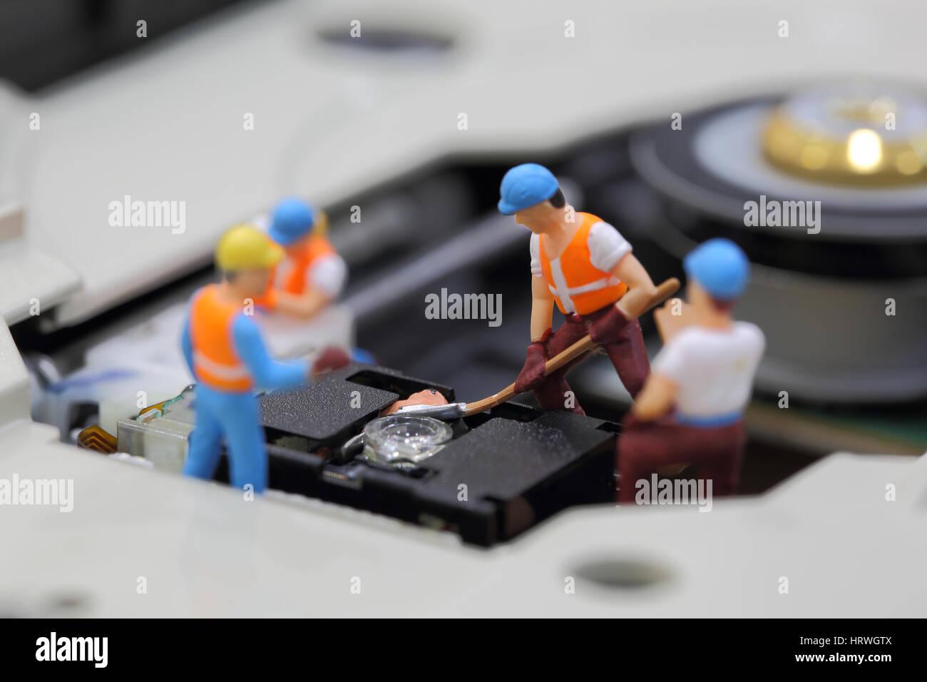 El enfoque selectivo de ingeniero en miniatura y trabajador fijo para limpiar el lector de CD ROM de la placa base Foto de stock