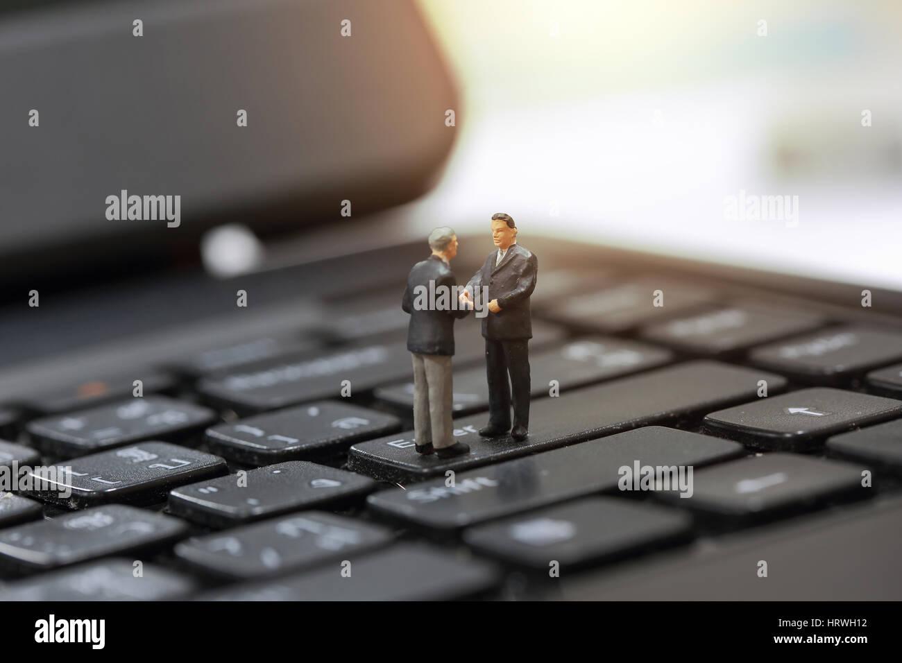 El enfoque selectivo de apretón de manos del empresario en miniatura sobre la inversión empresarial en el fondo Foto de stock