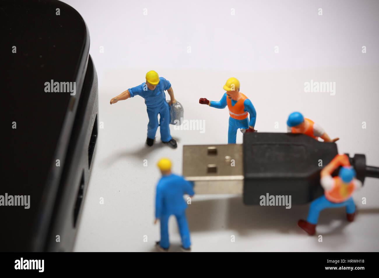 El enfoque selectivo de ingeniero en miniatura y trabajador plugin puerto USB al ordenador y utilizar para negocios Foto de stock