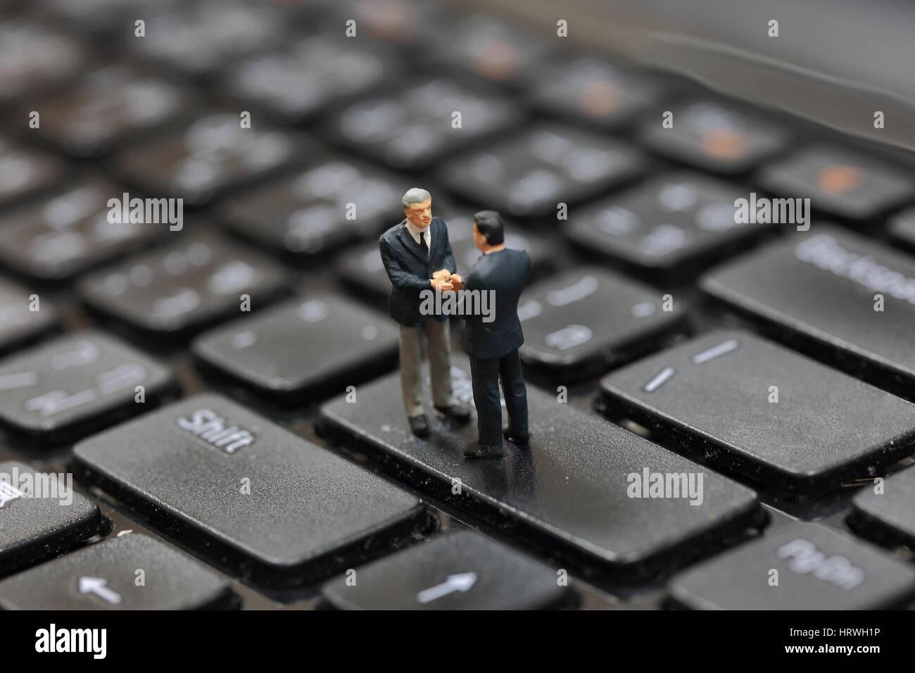El enfoque selectivo de hombre de negocios en miniatura de apretón de manos en el botón Enter del teclado portátil Foto de stock