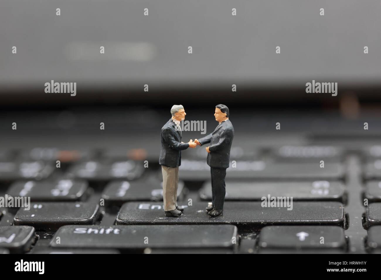 El enfoque selectivo de empresario en miniatura de apretón de manos en el botón Enter del teclado como compromiso Foto de stock