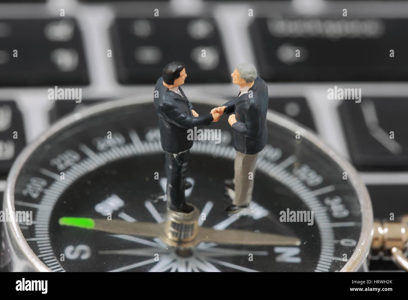 El enfoque selectivo de empresario en miniatura de apretón de manos en el fondo de la brújula como el compromiso Foto de stock