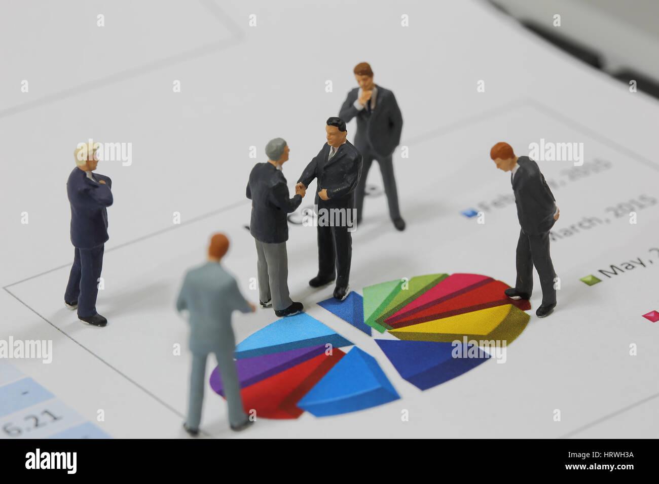 Vista superior el enfoque selectivo de hombre de negocios en miniatura de apretón de manos en círculo colorido fondo Foto de stock