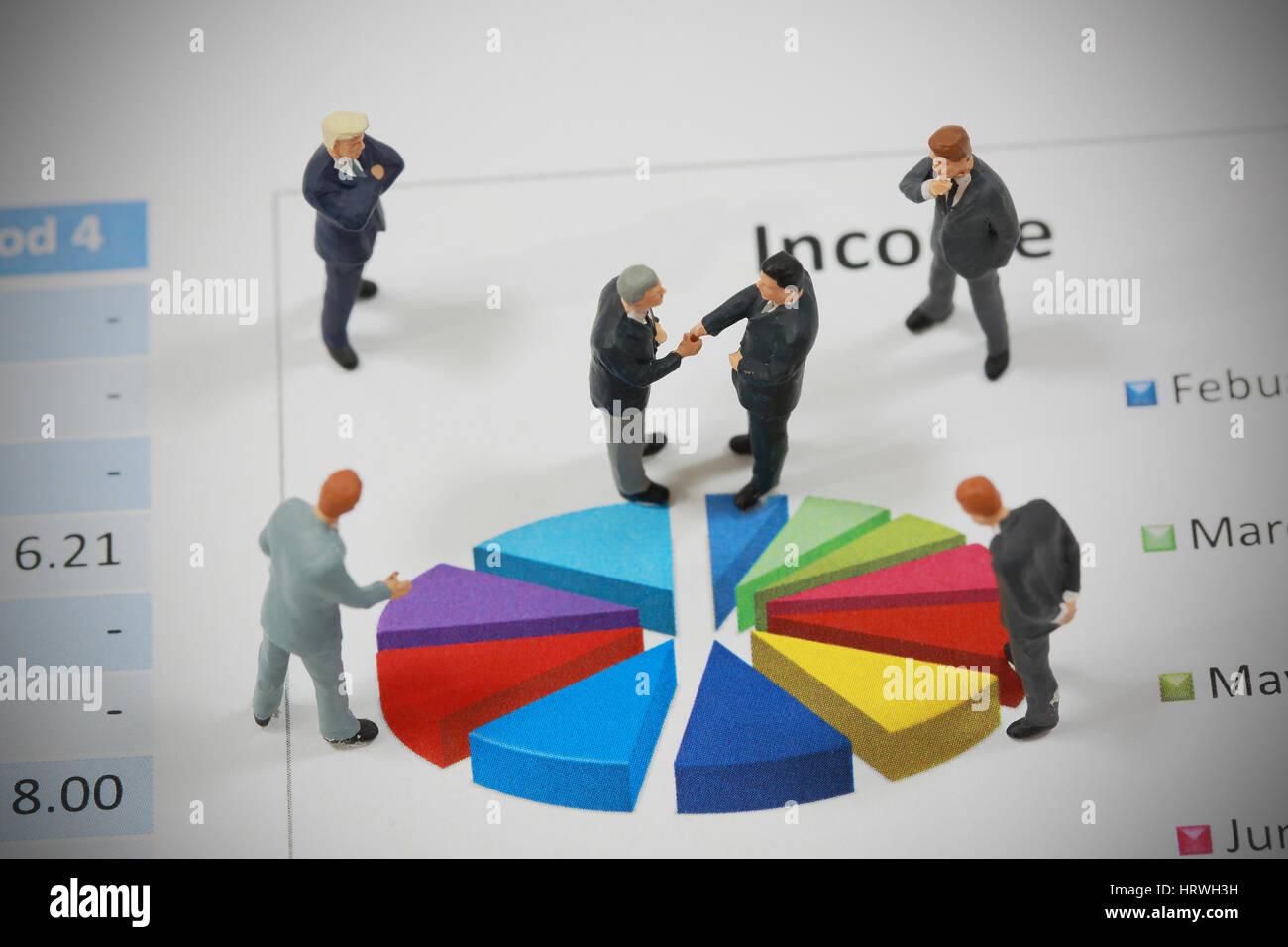 Vista superior el enfoque selectivo del empresario en miniatura de apretón de manos en el círculo de fondo gráfico Foto de stock