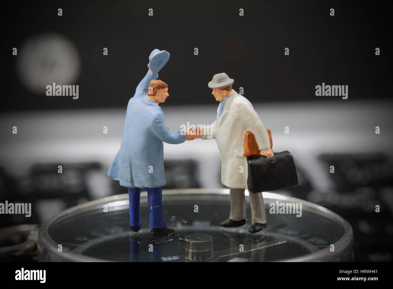 El enfoque selectivo de empresario en miniatura de apretón de manos en el fondo de la brújula como bienvenida y Foto de stock