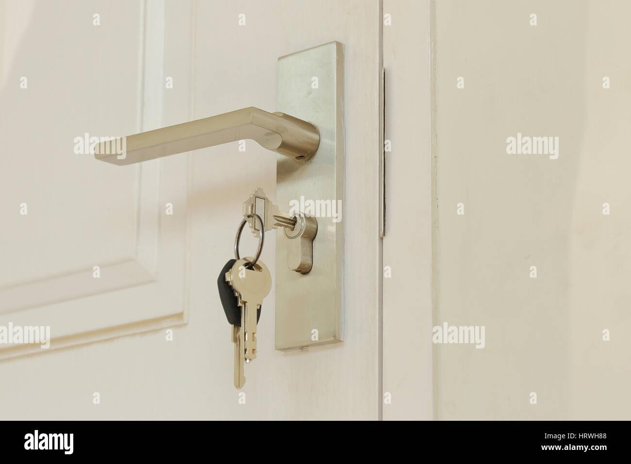 Insertar clave y mantenga en el pomo metálico de puerta blanca horizontal Foto de stock