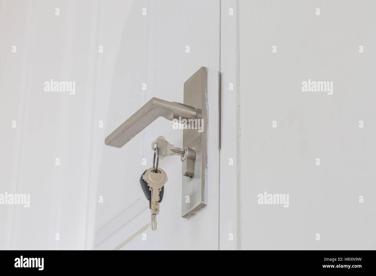 Insertar clave y mantenga en el pomo metálico de puerta blanca horizontal como cerrajero concepto. Foto de stock