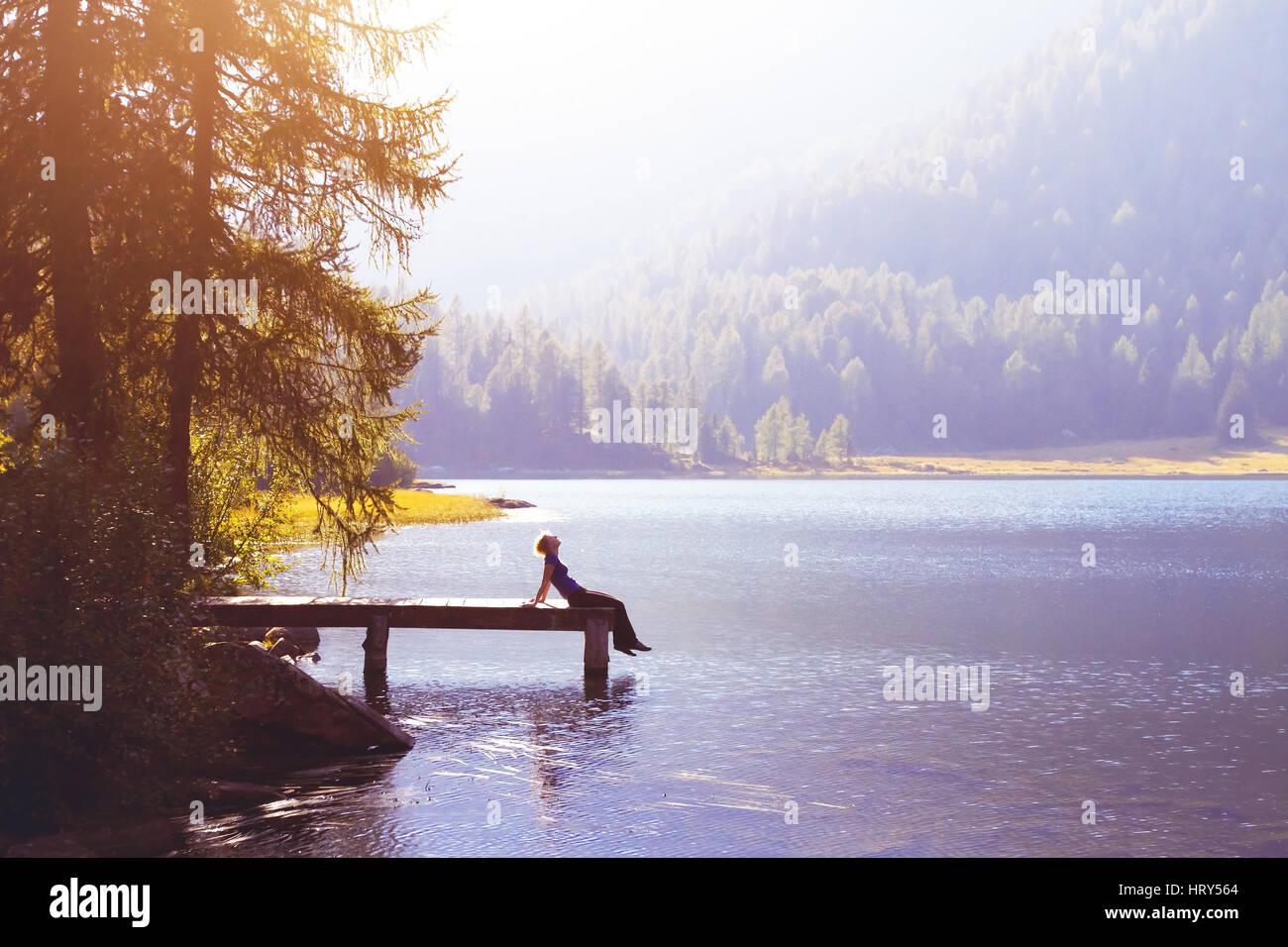 Feliz mujer sentada en el muelle y sonriente, felicidad o inspiración concepto, disfrutar de la vida Imagen De Stock