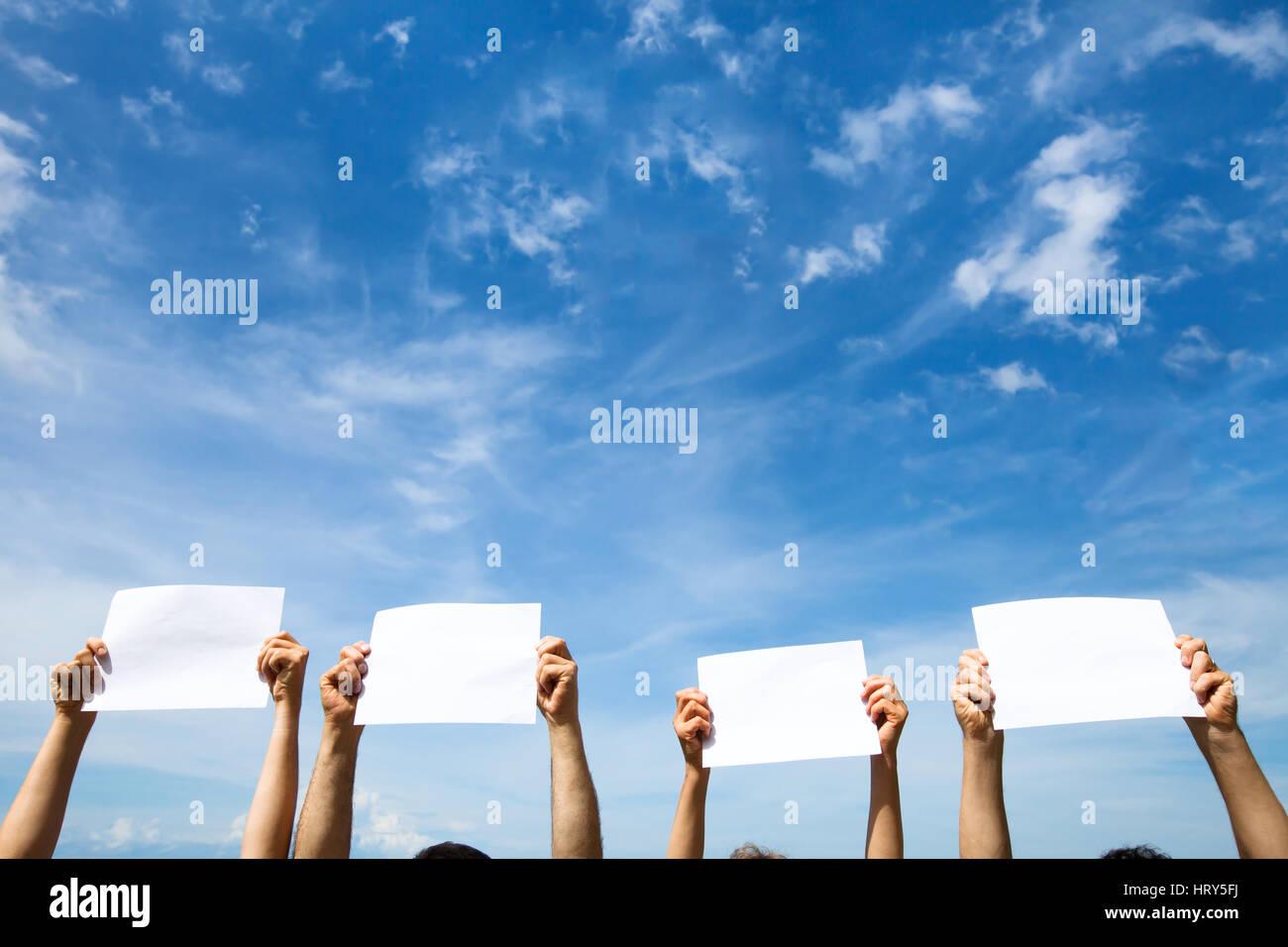 Grupo de personas sosteniendo carteles papel en blanco vacía sobre fondo de cielo azul Imagen De Stock
