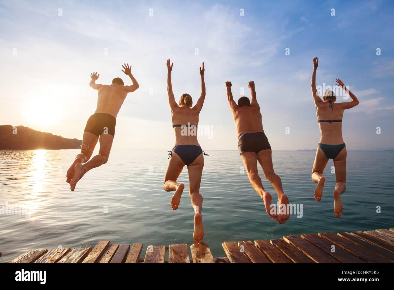 Grupo de Amigos saltando al mar desde el muelle, felices vacaciones en la playa Imagen De Stock