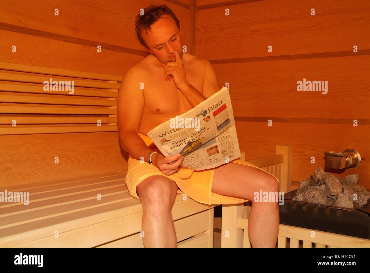 Mann liest Zeitung en Sauna - mujer en sauna Imagen De Stock