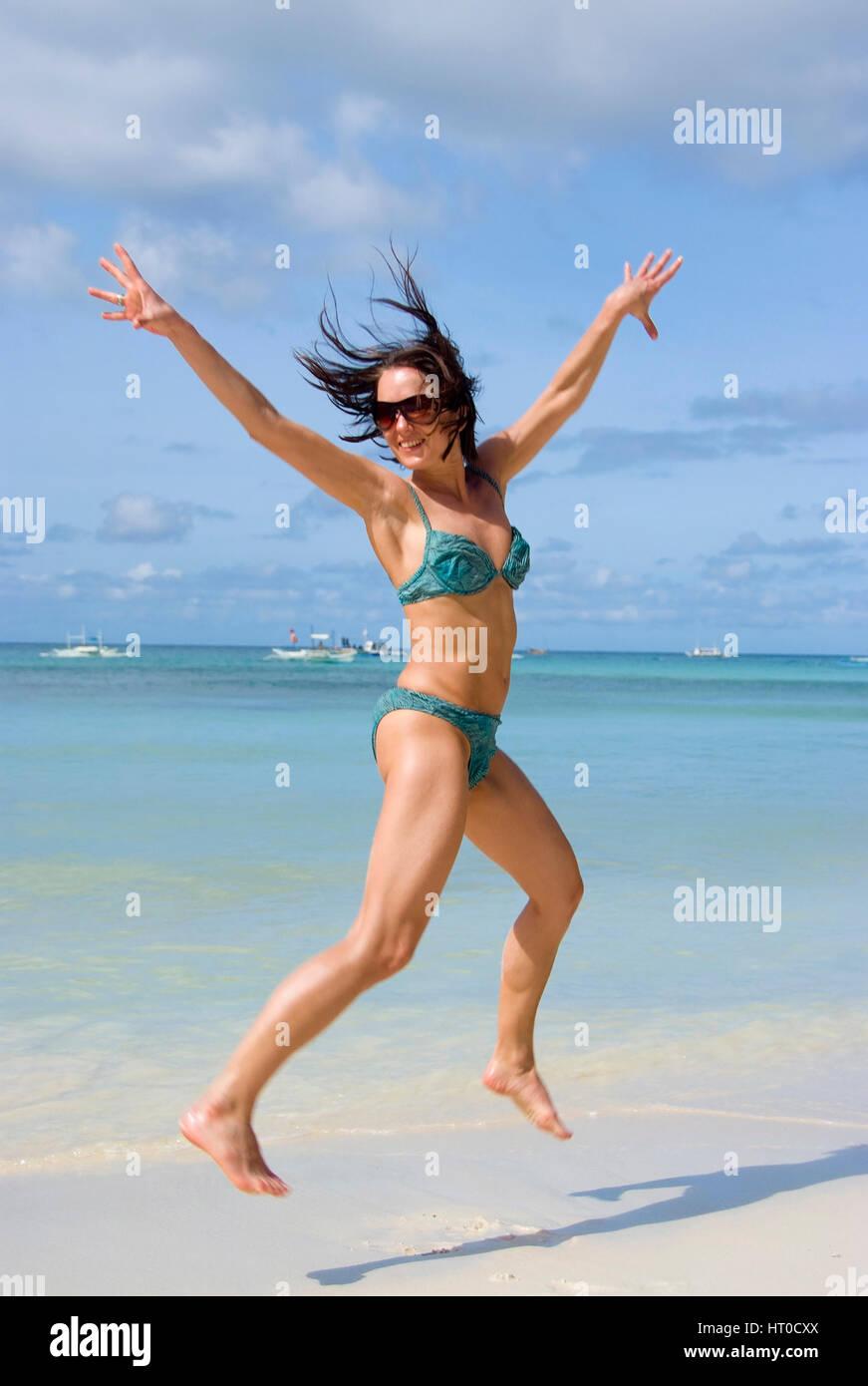 Junge, vitale Frau im Bikini springt am Strand - joven saltando en la playa Foto de stock