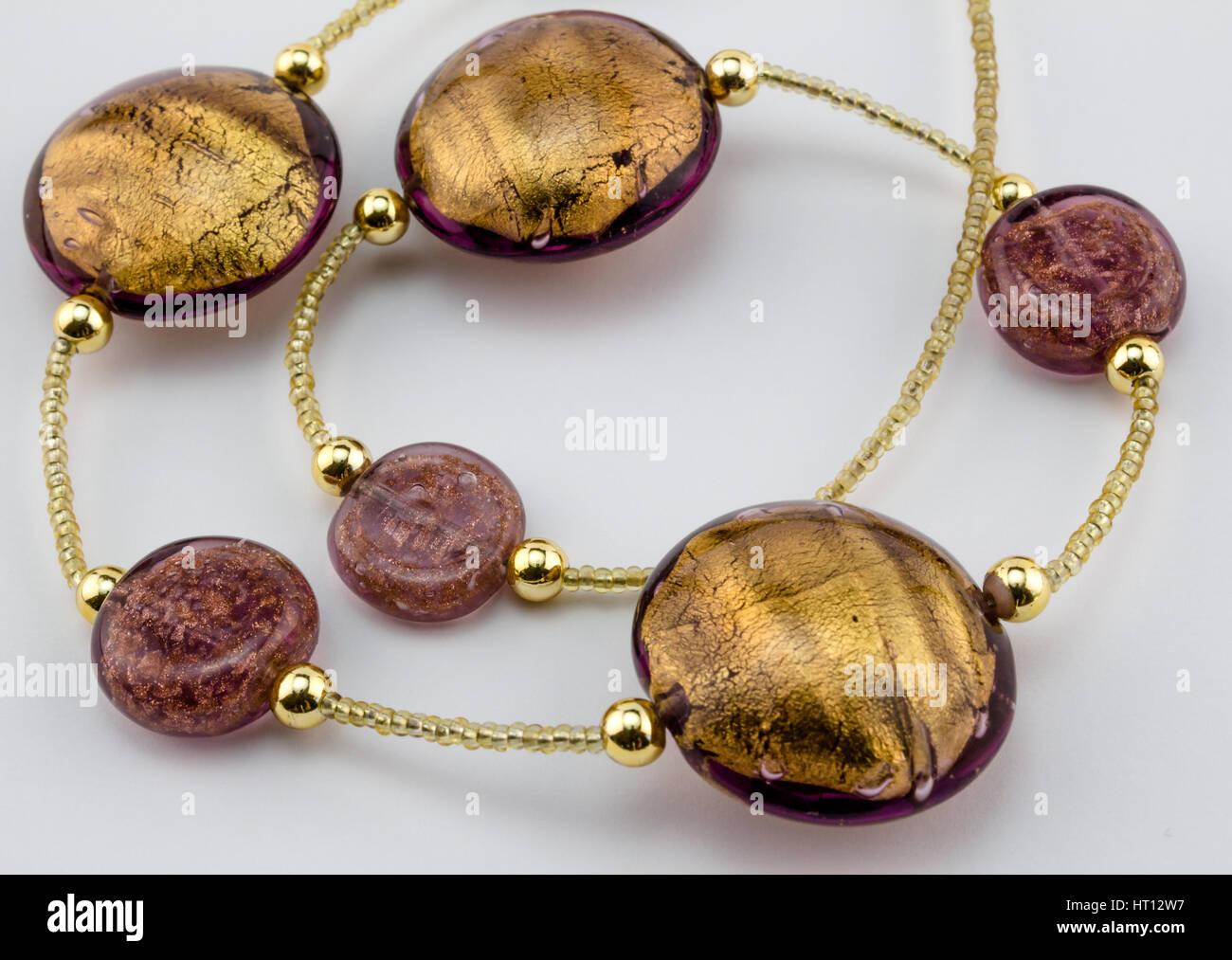 - Cristal de Murano collar de abalorios de oro de cerca sobre fondo blanco. Foto de stock
