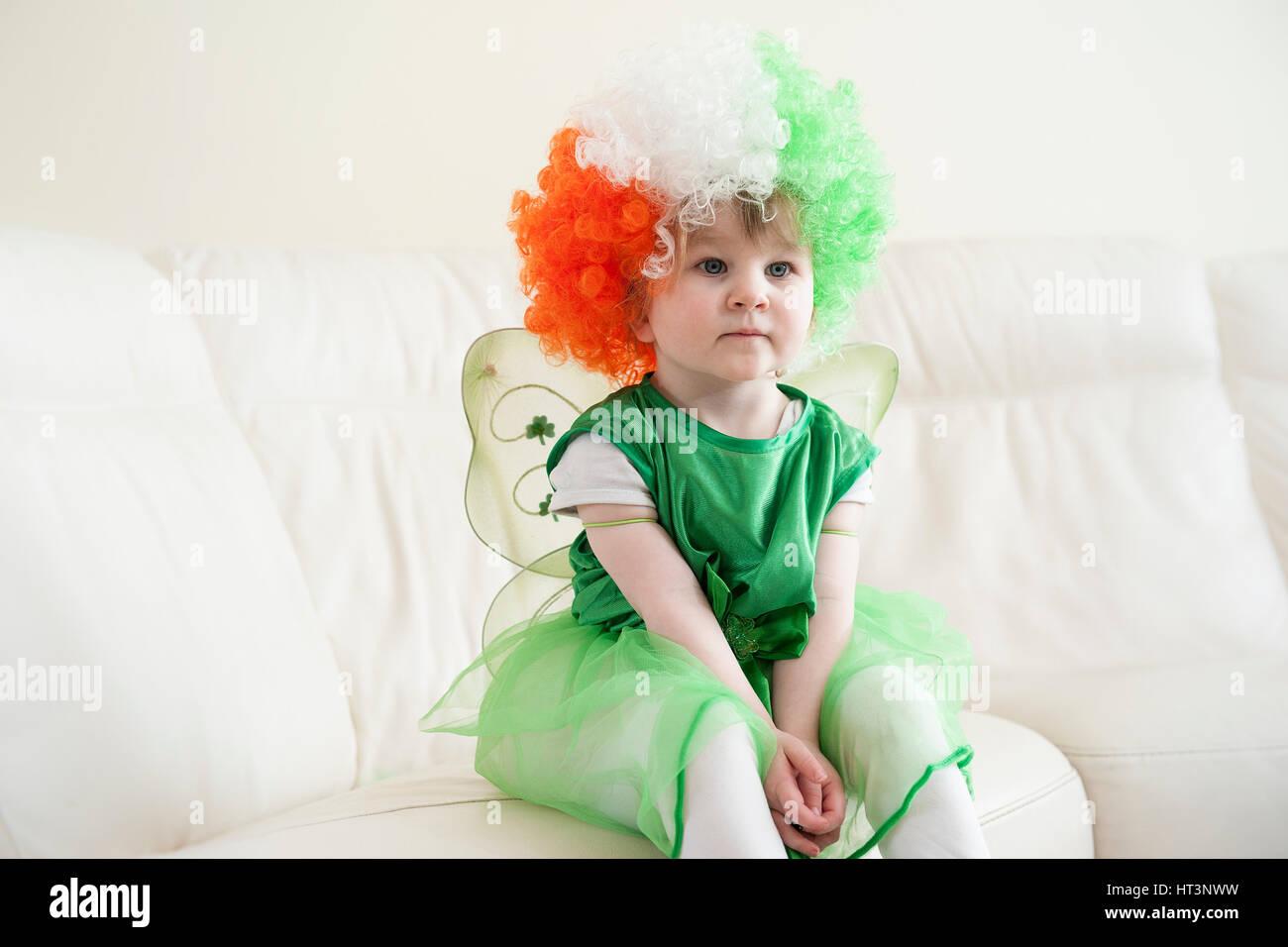 Un Asentado Cute Little Girl Con Una Peluca Con Los Colores