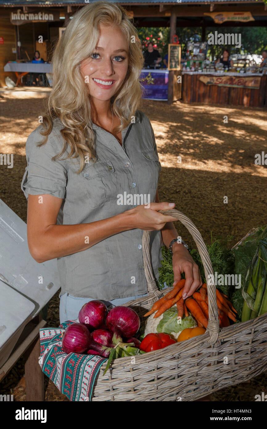 Una joven rubia de cabellos largos mujer adulta comprando productos frescos y saludables nutritivas en el mercado Imagen De Stock
