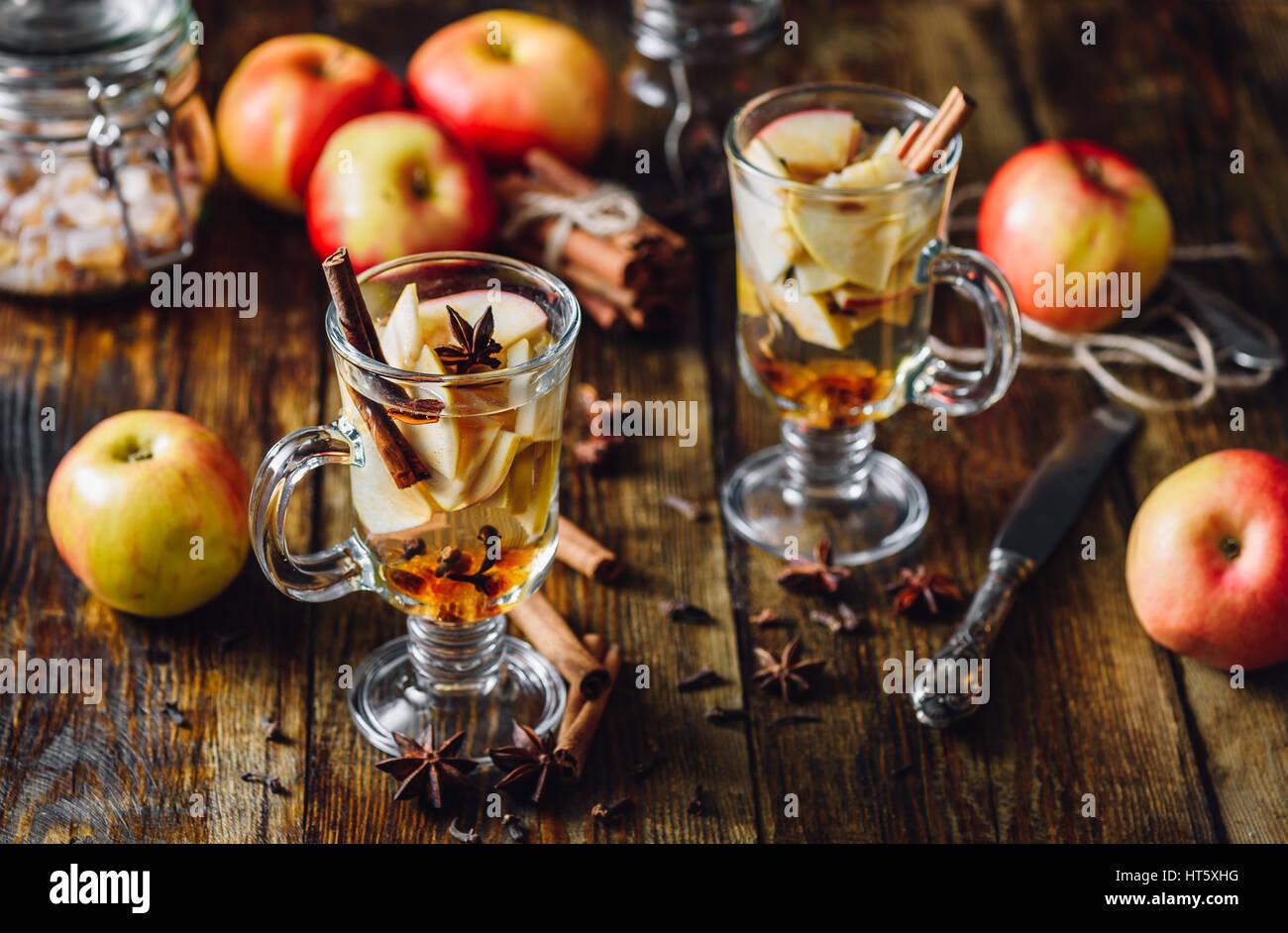 Casero bebidas condimentadas con tajadas de manzanas y algunas hierbas de cocina. Imagen De Stock