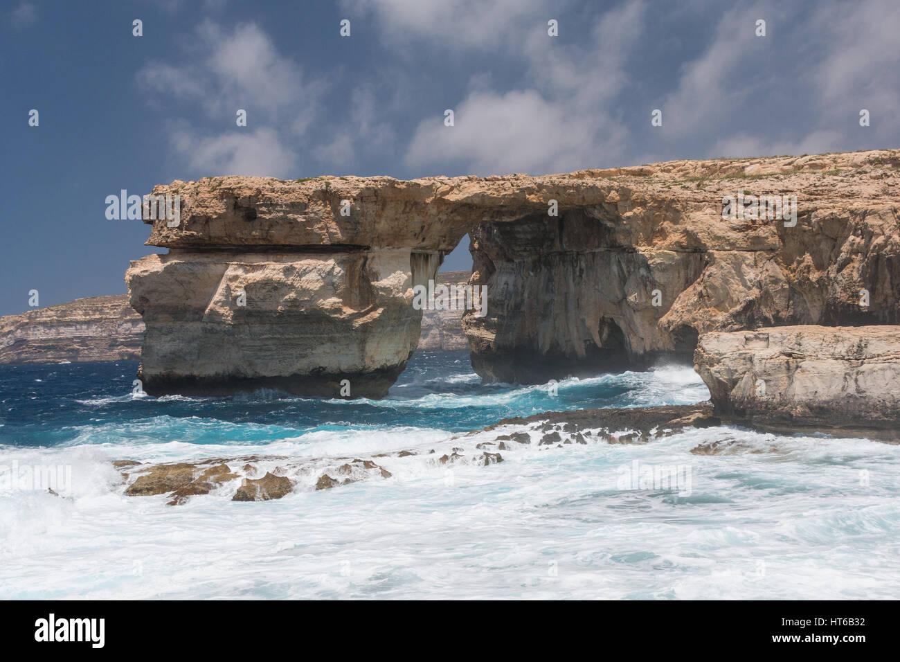 La ventana azul con el romper de las olas en el día, en Gozo, Malta Imagen De Stock