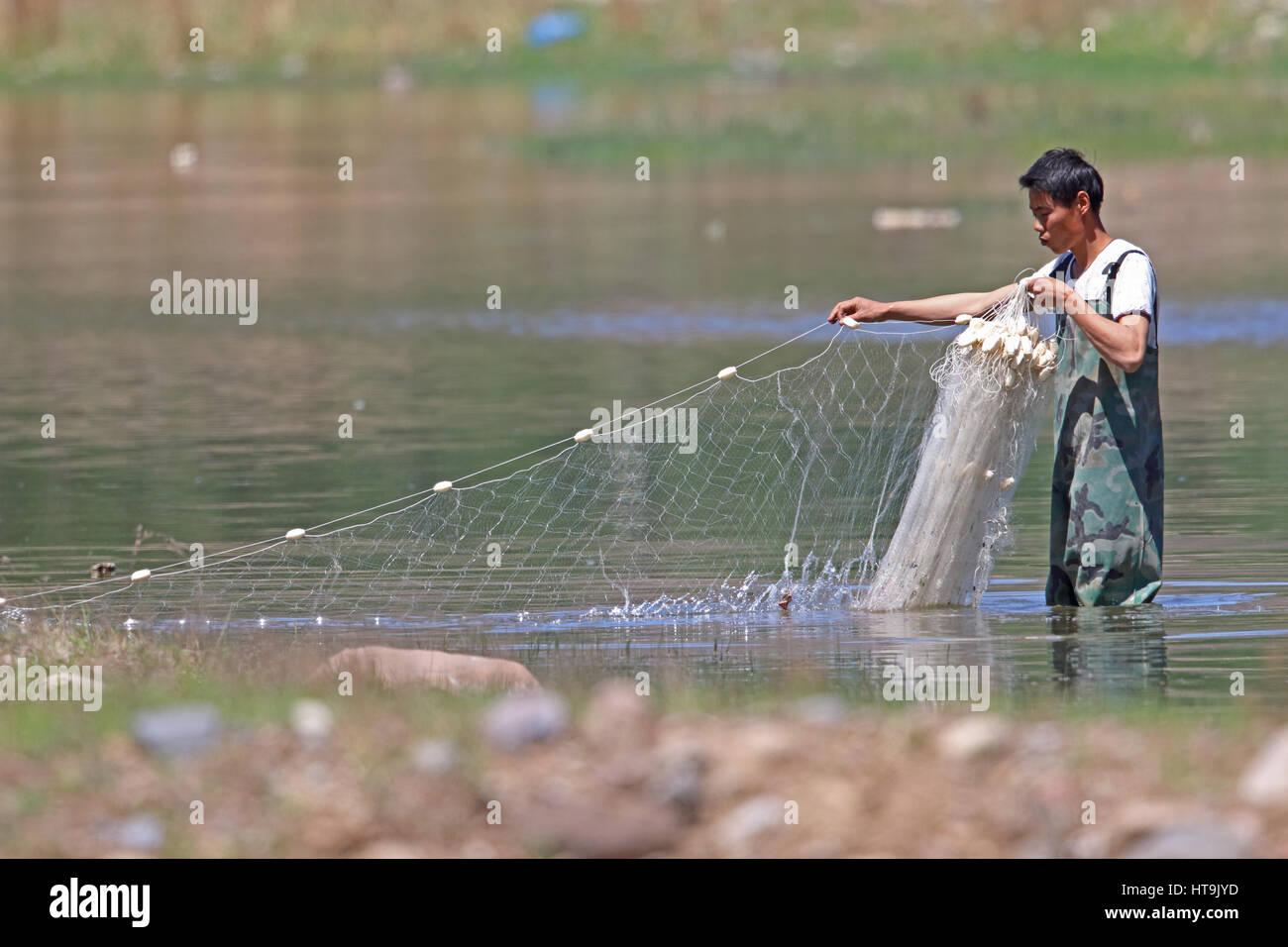 Ajuste de hombre net en río de montaña superficial Hebei, China puede Foto de stock