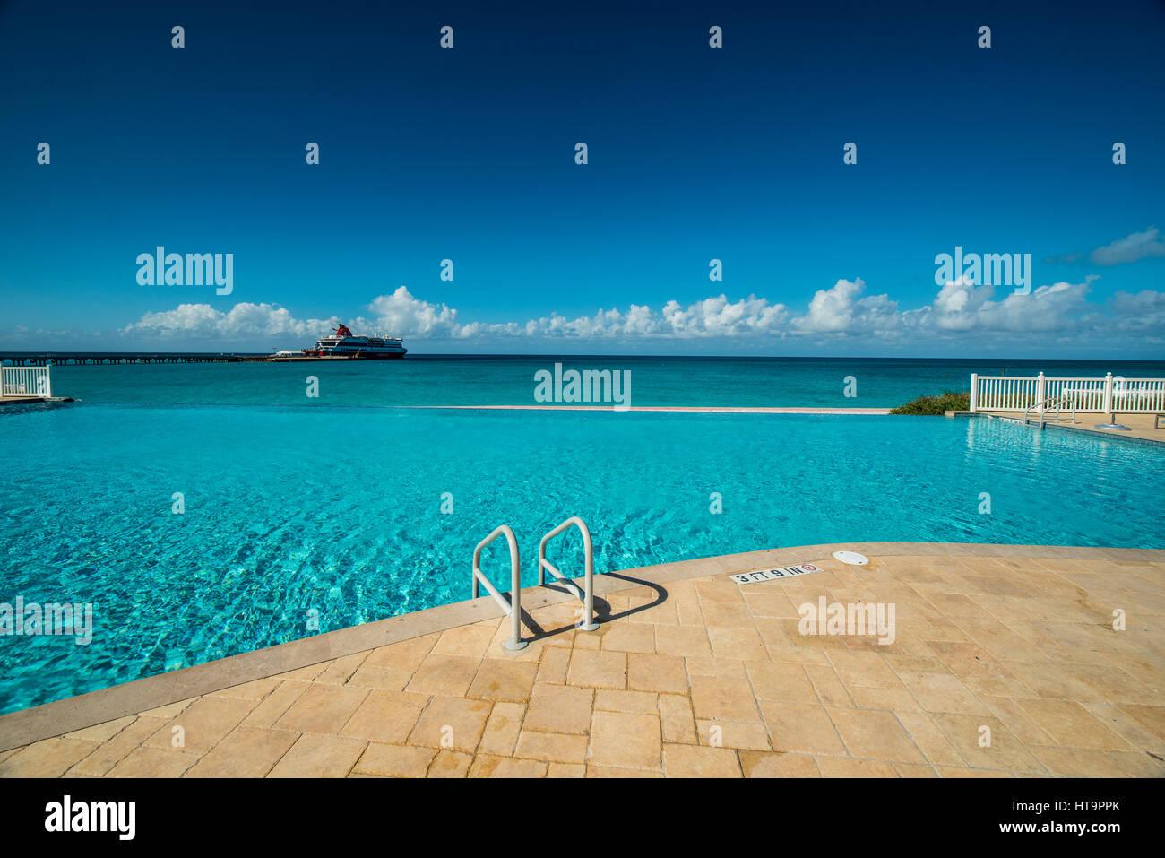 Piscina con agua azul océano azul y un crucero en la distancia Imagen De Stock