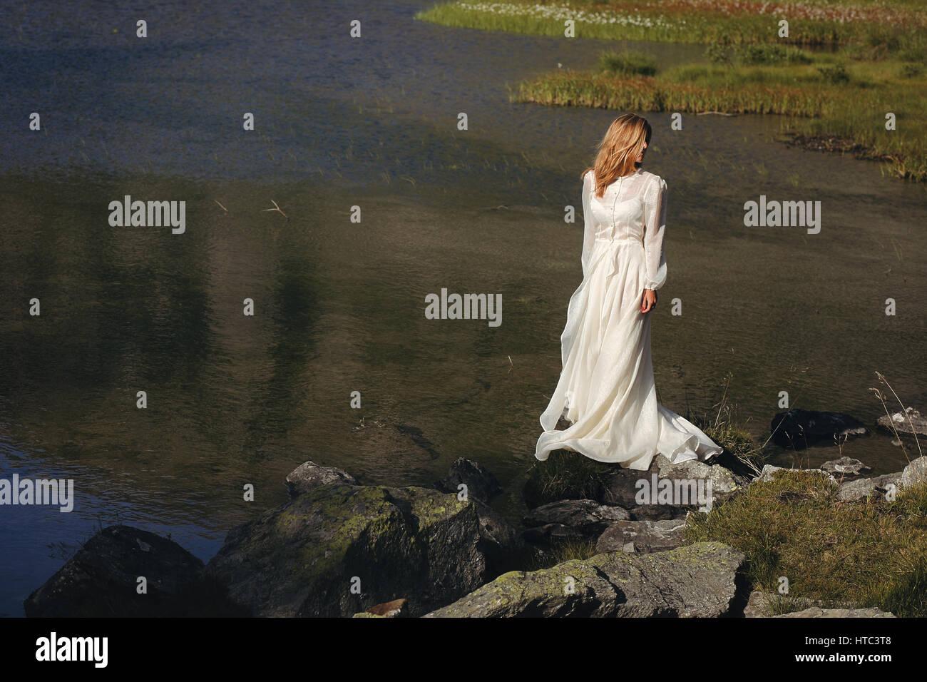 Triste novia posando en un lago de montaña. Romántica y soñadora Imagen De Stock