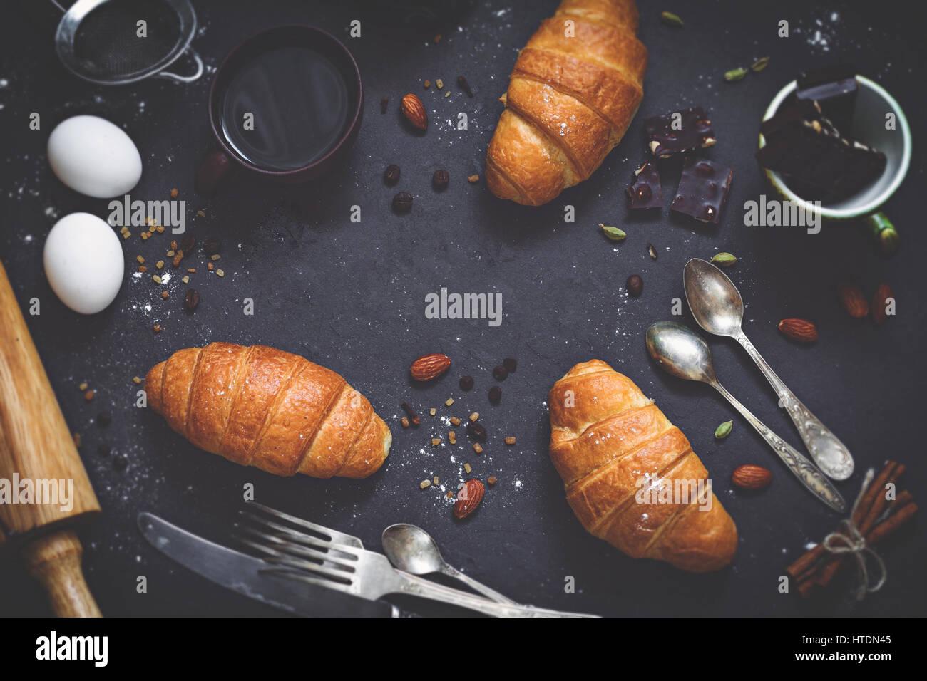 Café, cruasanes, chocolate, especias, nueces y vintage cubiertos. Composición de laicos plana dulce desayuno Imagen De Stock