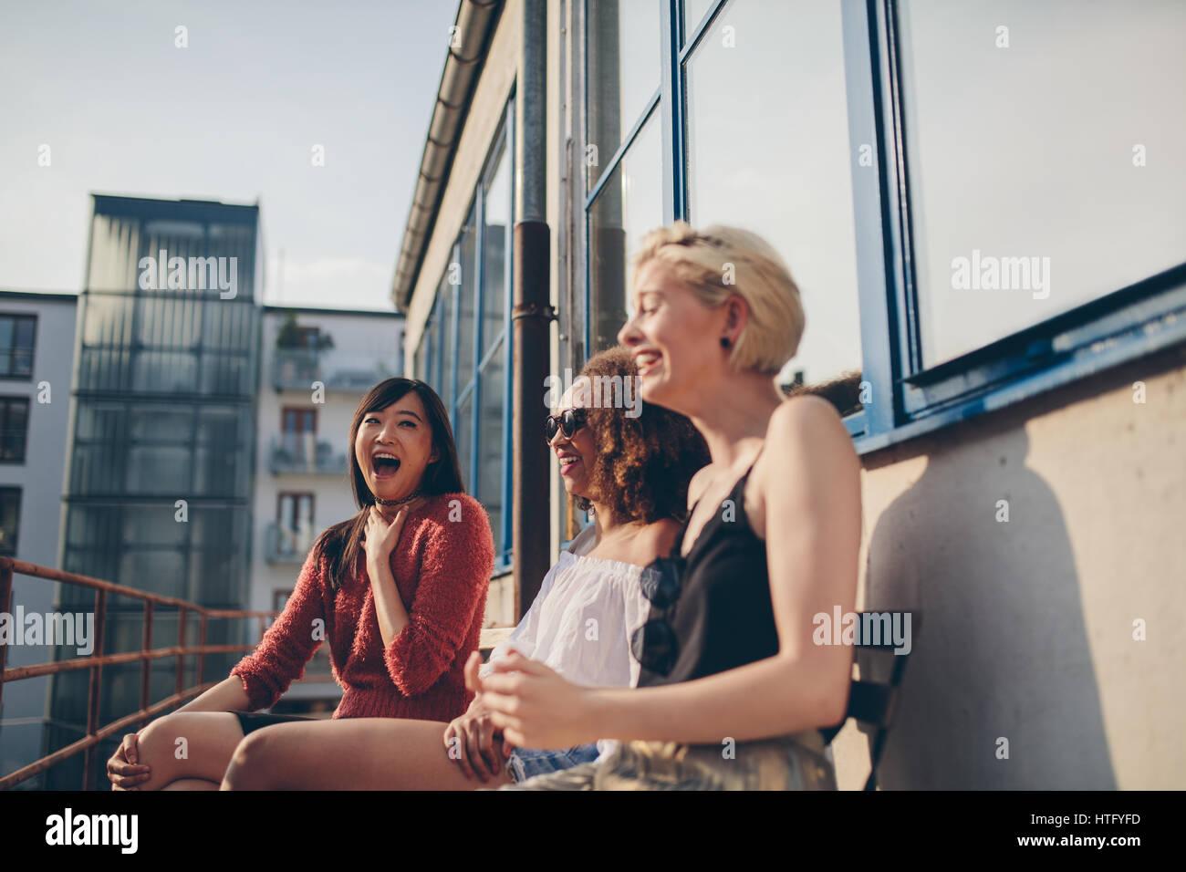Disparo de smiling amigas jóvenes sentados juntos en la terraza. Las mujeres multirraciales relajarse al aire Imagen De Stock