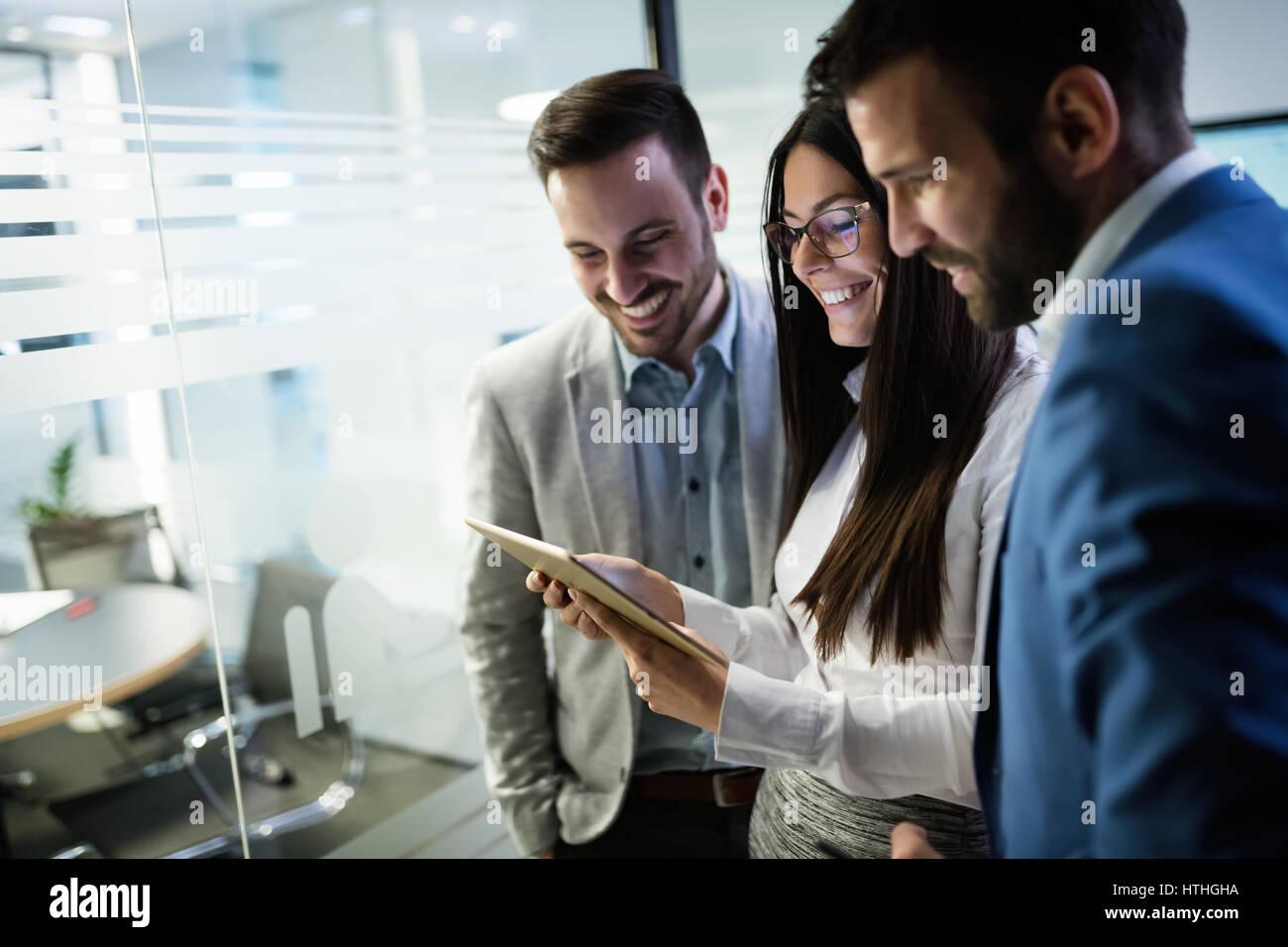 Gente de negocios feliz en la oficina mirando tablet Imagen De Stock