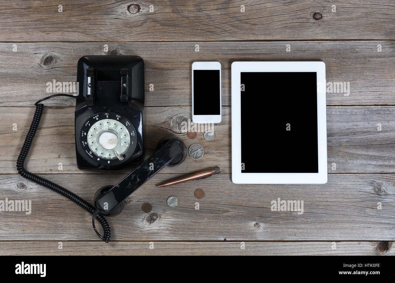 Vista aérea de un teléfono antiguo con modernos dispositivos inalámbricos para sustituirlo Foto de stock