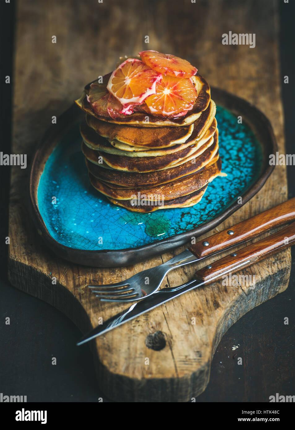 Tortitas con miel y sangrienta las rodajas de naranja sobre placa azul Imagen De Stock
