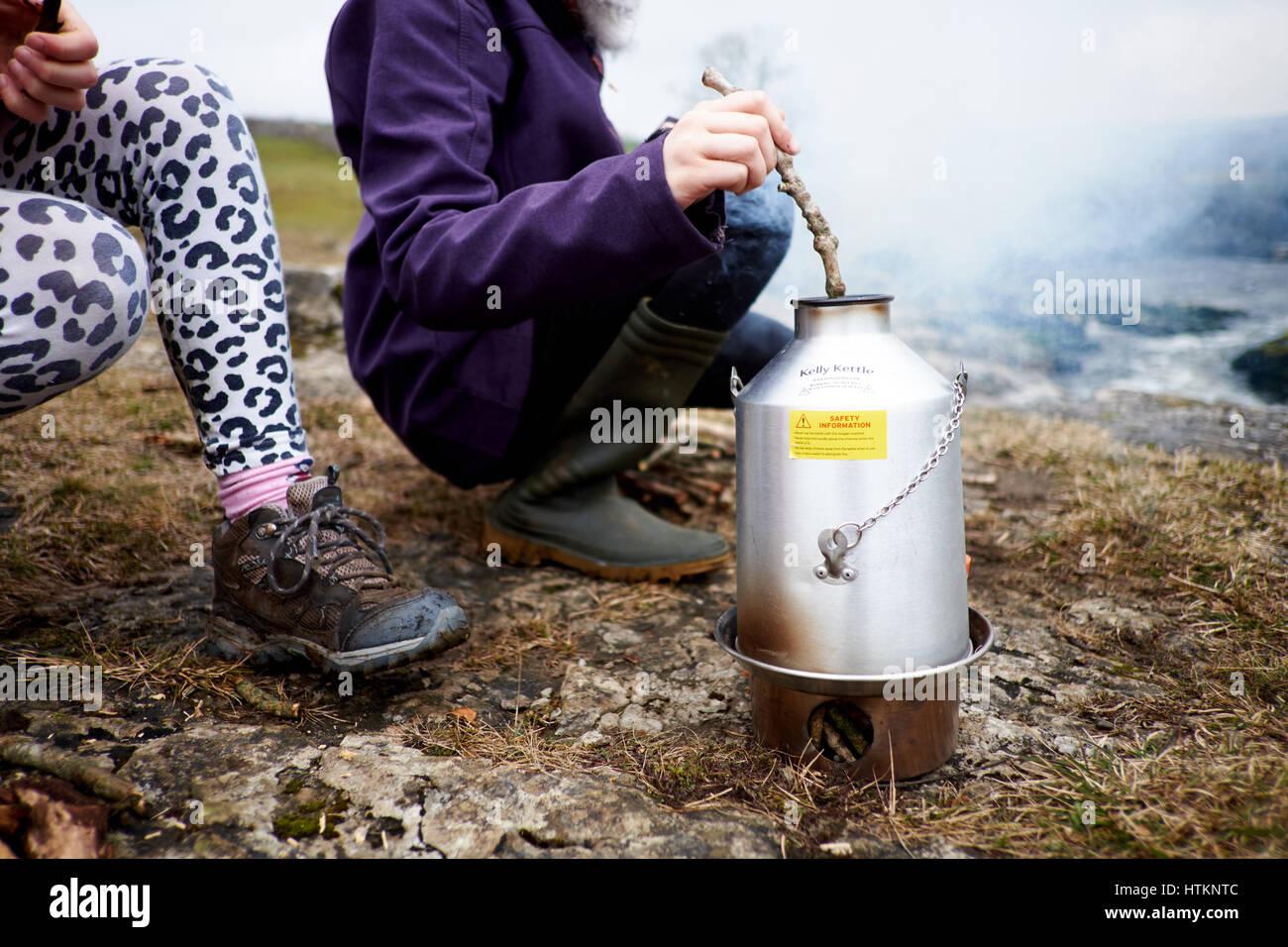 Dos niños al aire libre alrededor de una estufa de leña Kelly hervidor de agua hervidor de agua de alimentación Imagen De Stock
