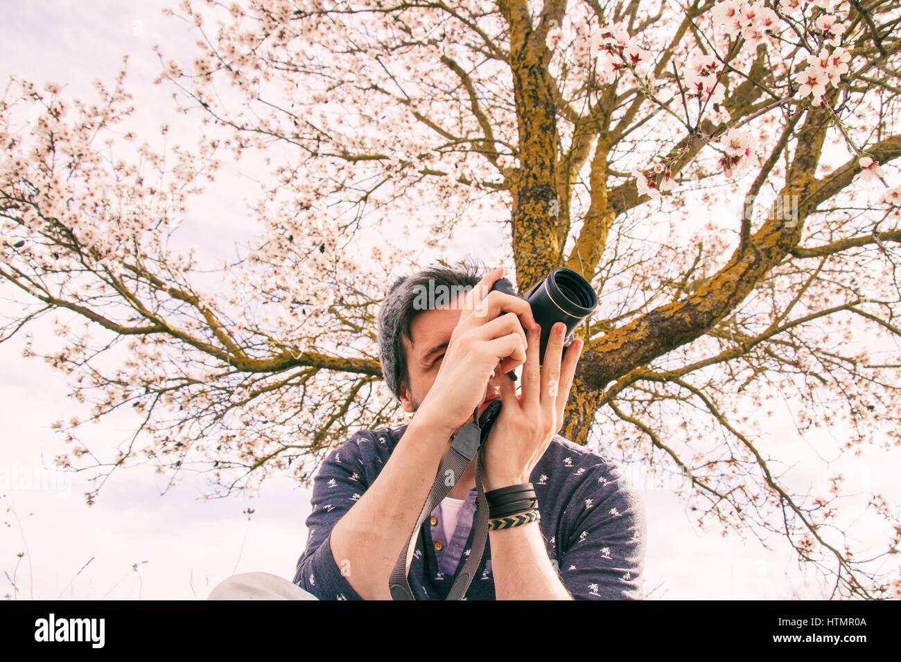 Young hipster hombre tomando fotos cerca de un árbol en flor en primavera Foto de stock