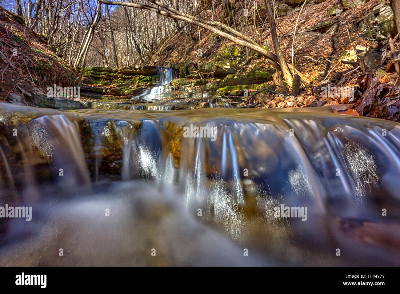 Cerrar vista del agua en el río pequeño con rocas en la montaña Foto de stock