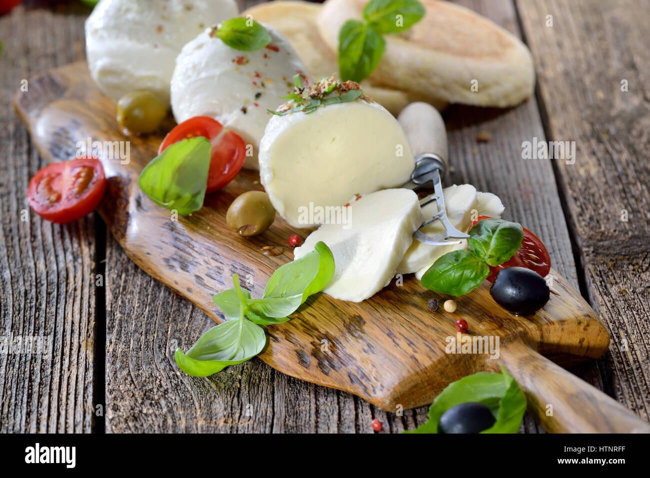 Queso mozzarella italiano snack con tomates cherry, albahaca y aceitunas servido sobre una tabla de madera con tostadas Foto de stock