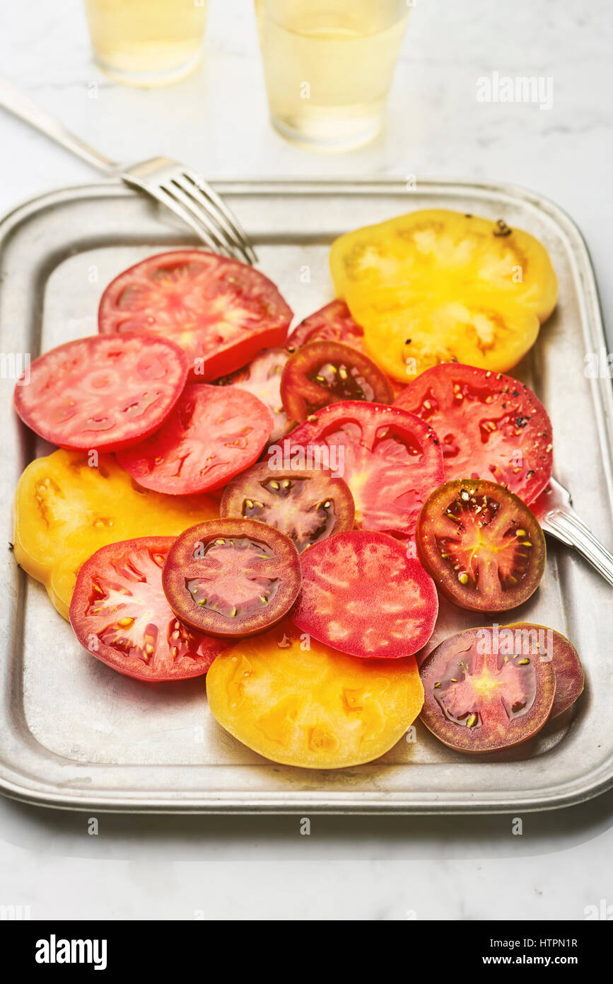 Disparo vertical sencilla ensalada de tomate servida en plato de plata Imagen De Stock