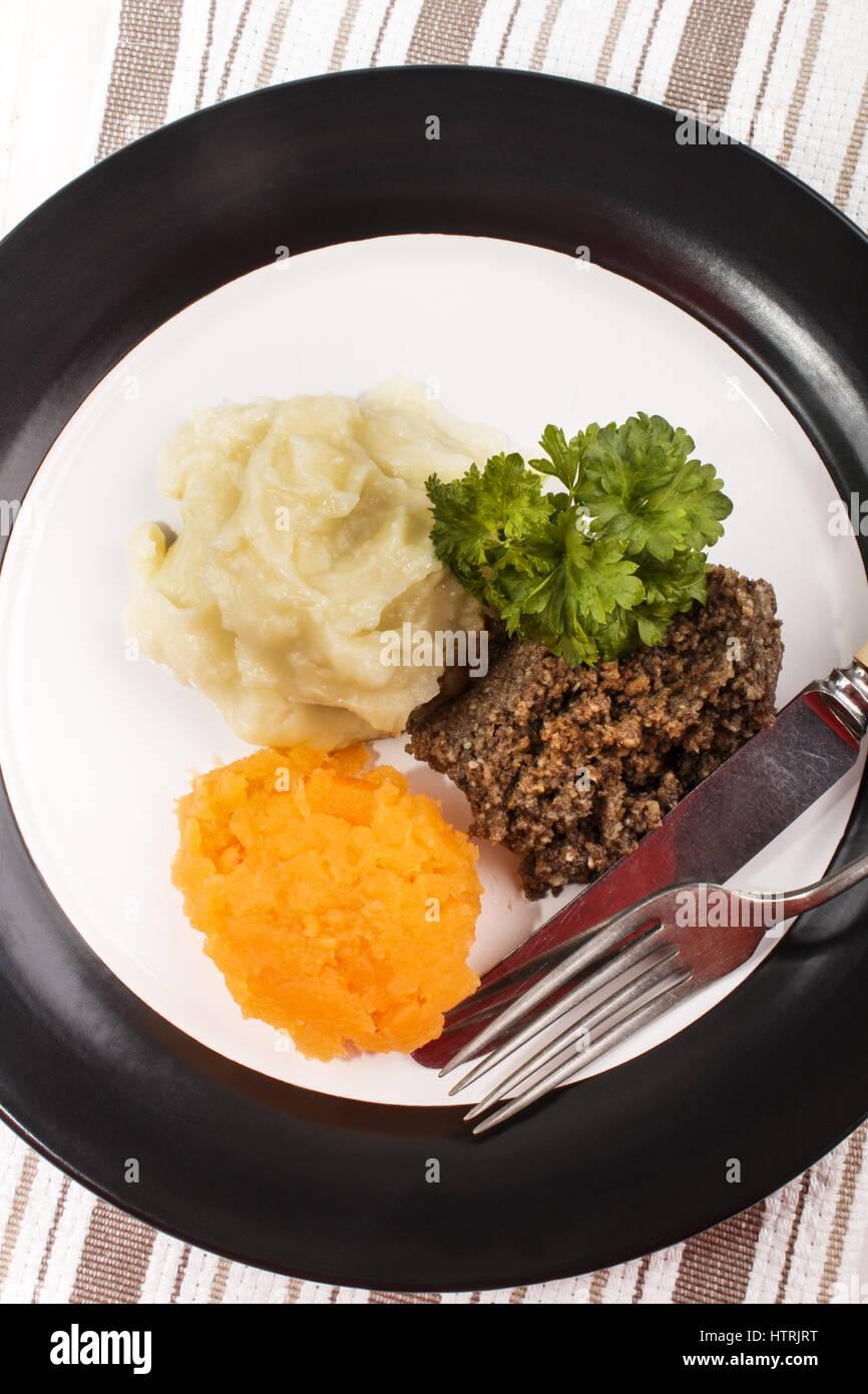 Plato típico escocés, haggis con puré de patatas, nabos y perejil en una placa Foto de stock