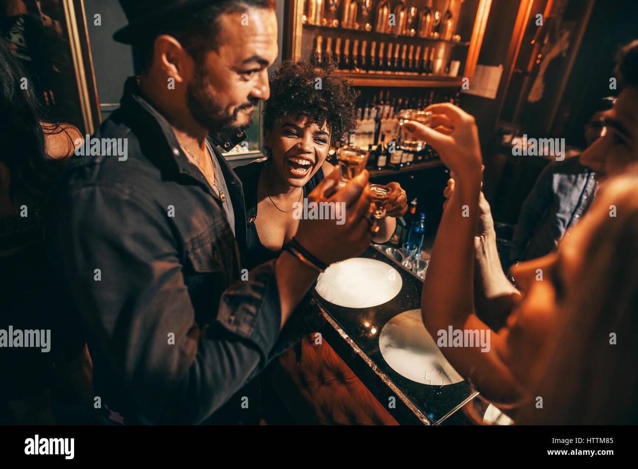 Los jóvenes feliz divirtiéndose con bebidas en la discoteca. Hombre y mujer bebiendo en el bar. Imagen De Stock