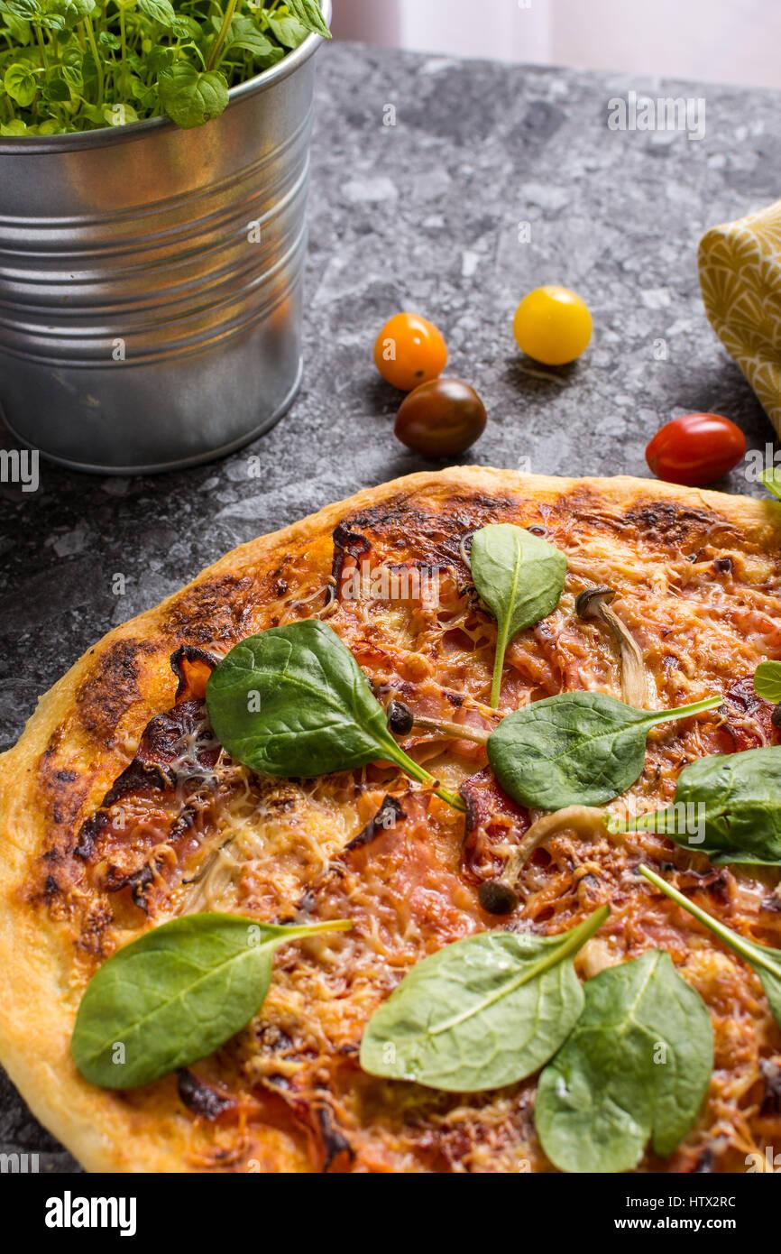 Pizza casera con queso, jamón, salami, Baby espinacas y setas shimeji. Horneado fresco italiano de alimentos Imagen De Stock