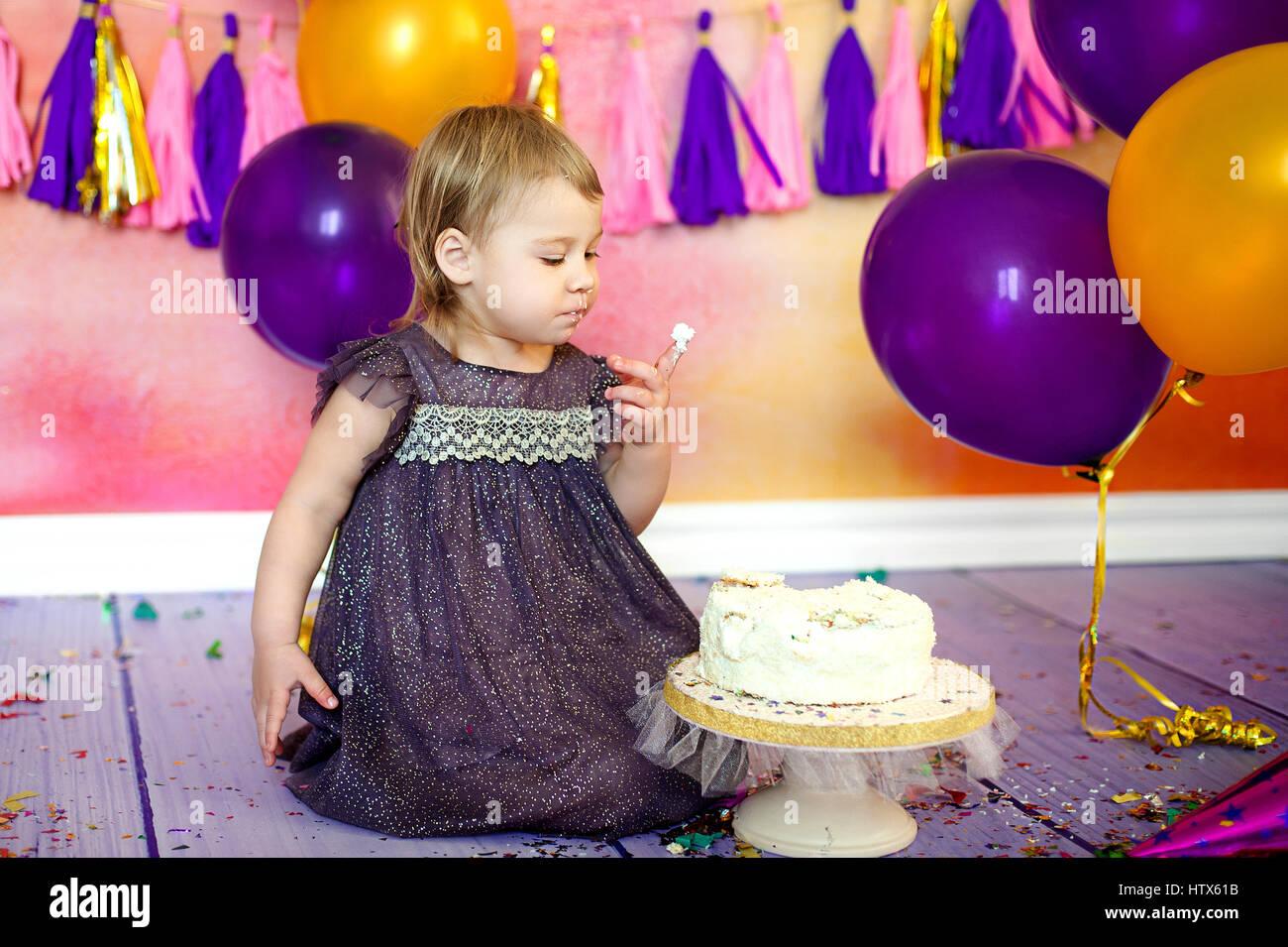 Bebé de dos años comiendo pastel. Fiesta de cumpleaños. Decoración guirnaldas y globos Imagen De Stock