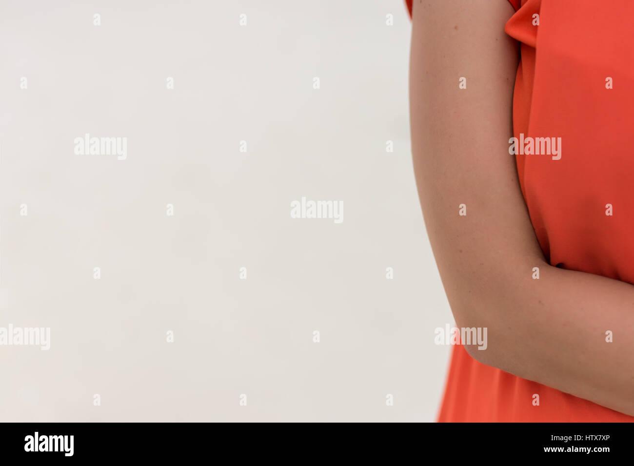 Brazo derecho de la mujer joven y vestido de naranja con espacio de copia. Imagen De Stock