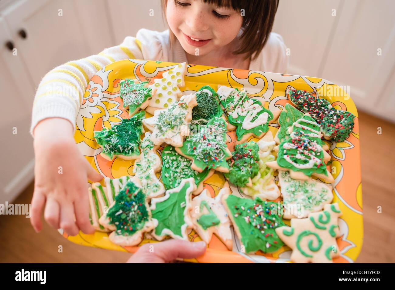 Chica sacando una cookie de Navidad Imagen De Stock